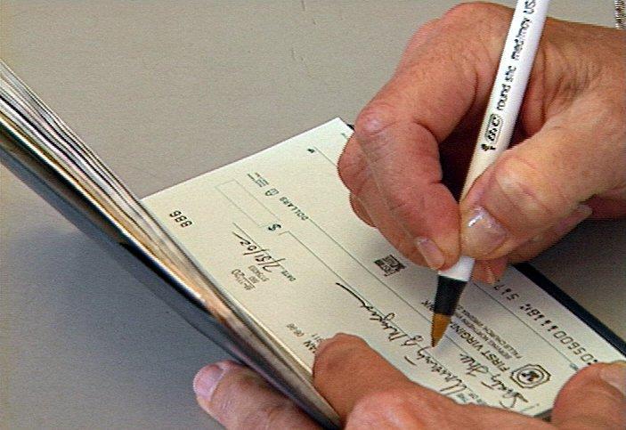 Person Writing in Checkbook